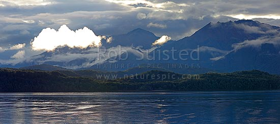 Lake Te Anau and Fiordland, with the Murchison Mountains beyond as mist lifts in the evening. Mt Owen centre. Panorama, Fiordland National Park, Southland District, Southland Region, New Zealand (NZ) stock photo.