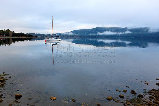 Sailboat moored on Lake Te Anau on a calm winter morning, with perfect reflection. Fiordland National Park beyond, Te Anau, Southland District, Southland Region, New Zealand (NZ) stock photo.