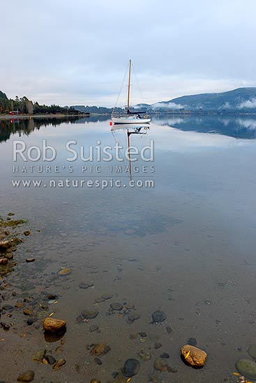 Sailboat moored on Lake Te Anau on a calm winter morning, with perfect reflection, Te Anau, Southland District, Southland Region, New Zealand (NZ) stock photo.