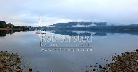 Sailboat moored on Lake Te Anau on a calm winter morning, with perfect reflection. Fiordland National Park beyond. Panorama, Te Anau, Southland District, Southland Region, New Zealand (NZ) stock photo.