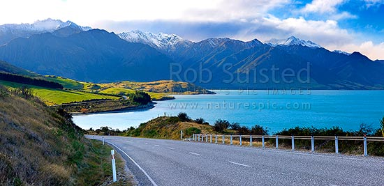 Lake Hawea in beautiful sunlight, with State Highway 6 (Makarora Lake Hawea Road) heading for Haast Pass. Panorama, Lake Hawea, Otago, Queenstown Lakes District, Otago Region, New Zealand (NZ) stock photo.