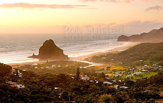 Piha Beach with Lion Rock prominent in the small west coast village surrounded by the Waitakere ranges at sunset. Te Waha Point and Kohunui Bay distant, Piha Beach, Auckland, Waitakere City District, Auckland Region, New Zealand (NZ) stock photo.
