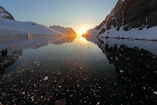 Lemaire Channel, Antarctica. Perfect reflections with midnight sunset, under beautiful peaks and brash ice, Antarctic Peninsula, Antarctica Region, Antarctica stock photo.