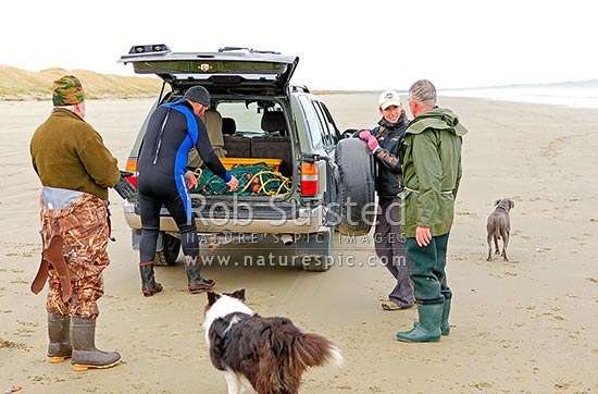 Local recreational flounder fishermen taking with a person walking dogs on Oreti Beach, Invercargill, Southland District, Southland Region, New Zealand (NZ) stock photo.