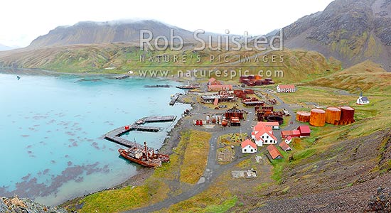 Grytviken whaling station remains in King Edward Cove. Whaling boats 'Dias' and 'Albatross' and museum foreground, and whalers church at left. Panorama, King Edward Cove, South Georgia stock photo.