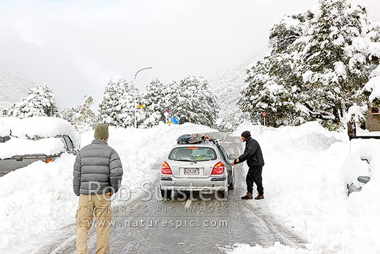 Arthur's Pass township in heavy winter snow. State Highway 73 to West Coast with skiers driving rental car on single open road lane, Arthur's Pass National Park, Selwyn District, Canterbury Region, New Zealand (NZ) stock photo.