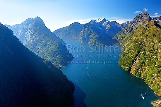 Looking down Milford Sound / Piopiotahi from near entrance. Sinbad Gully and Mitre Peak (1683m) left, The Lion (1302m), Mount Pembroke (2015m) centre, and Harrison Cove and Mills Peak right. Aerial panorama, Milford Sound, Fiordland National Park, Southland District, Southland Region, New Zealand (NZ) stock photo.
