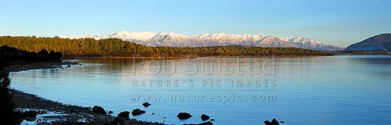 Lake Manapouri panorama looking towards to snowy Takitimu Mountains range in winter. Manapouri township far right, Manapouri, Southland District, Southland Region, New Zealand (NZ) stock photo.