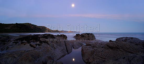 Port Awanui moonrise reflected in rockpool. Te Wharau Beach, Whakaumu Peak, East Cape and East Island (Whangaokeno) visible in distance. Panorama, Port Awanui, East Coast, Gisborne District, Gisborne Region, New Zealand (NZ) stock photo.