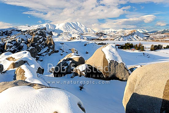 Castle Hill Station in heavy winter snows. Castle Hill limestone rock climbing area foreground. Craigieburn Range distant, Castle Hill, Selwyn District, Canterbury Region, New Zealand (NZ) stock photo.