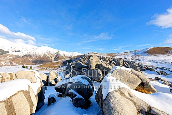 Castle Hill Station in heavy winter snows. Castle Hill limestone rock climbing area foreground. Torlesse Range left, Castle Hill, Selwyn District, Canterbury Region, New Zealand (NZ) stock photo.