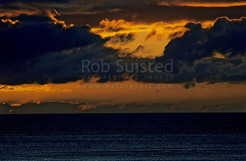 Fiery sunset over sea, Pukerua Bay, New Zealand (NZ) stock photo.