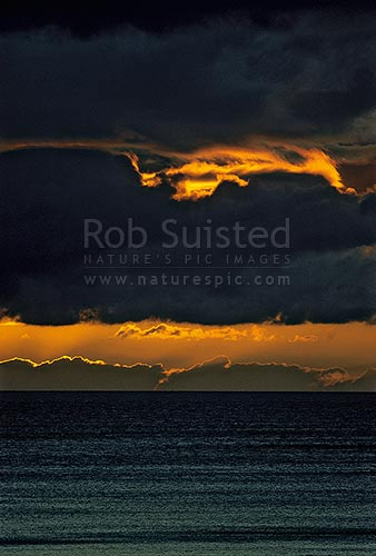 Fiery sunset over sea, Pukerua Bay, Porirua City District, Wellington Region, New Zealand (NZ) stock photo.