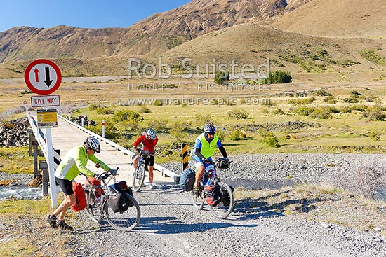 Mountain bike riders on a multiday touring trip, Wairau River bridge on the Rainbow Road, near Sedgemere, Molesworth Station, Marlborough District, Marlborough Region, New Zealand (NZ) stock photo.