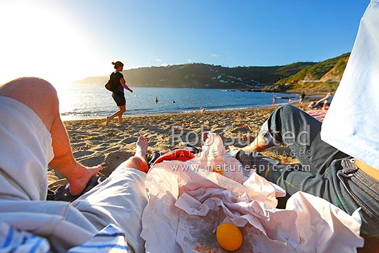Wellington south coast Princess Bay Beach, with people enjoying a summer evening meal of fish and chips watching the sun set, Houghton Bay, Wellington City District, Wellington Region, New Zealand (NZ) stock photo.