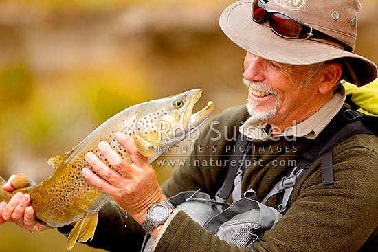 Malcolm Bell and brown trout after a successful catch, Molesworth Station, Marlborough District, Marlborough Region, New Zealand (NZ) stock photo.