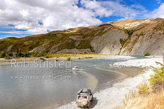 Clarence River Valley, with four wheel drive vehicles crossing the Clarence ford below Quail Flat. Limestone Hill behind, Clarence Reserve, Kaikoura District, Canterbury Region, New Zealand (NZ) stock photo.