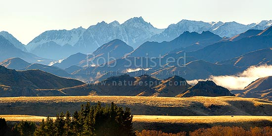 Mount Tapuae-o-Uenuku (2885m) and Inland Kaikoura Ranges panorama on a calm golden Autumn morning as mist lifts from valleys, Molesworth Station, Marlborough District, Marlborough Region, New Zealand (NZ) stock photo.