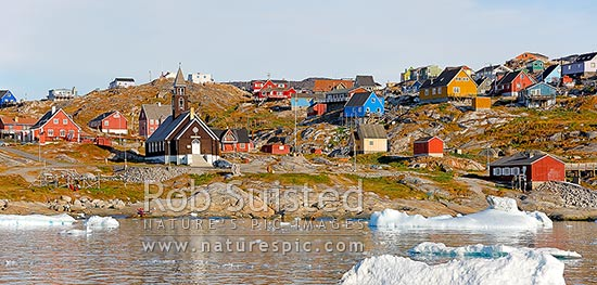 Ilulissat township seen from the sea, with Zion's church (1779) prominent in the bay, with bright coloured houses on hills. Panorama, Ilulissat, Greenland stock photo.