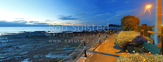Tahunanui Beach waterfront walkway along Rocks Road and Wakefield Quay, with person watching sunset over Tasman Bay. Panorama, Nelson, Nelson City District, Nelson Region, New Zealand (NZ) stock photo.
