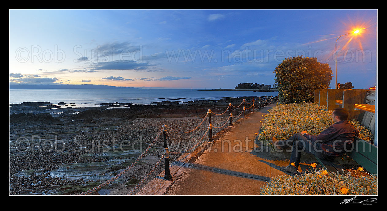 Image of Tahunanui Beach waterfront walkway along Rocks Road and Wakefield Quay, with person watching sunset over Tasman Bay. Panorama, Nelson, Nelson City District, Nelson Region, New Zealand (NZ) stock photo image