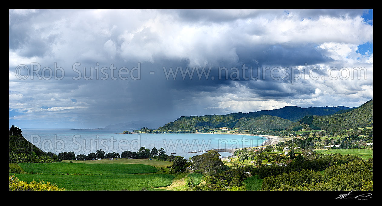 Image of Looking across Omaio Bay, Otuwhare and Omaio township towards Te Kaha Point in distance, with weather rain storm cloud over Okahu Point and coast. Panorama, Te Kaha, East Cape, Opotiki District, Bay of Plenty Region, New Zealand (NZ) stock photo image
