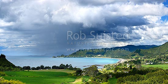 Looking across Omaio Bay, Otuwhare and Omaio township towards Te Kaha Point in distance, with weather rain storm cloud over Okahu Point and coast. Panorama, Te Kaha, East Cape, Opotiki District, Bay of Plenty Region, New Zealand (NZ) stock photo.