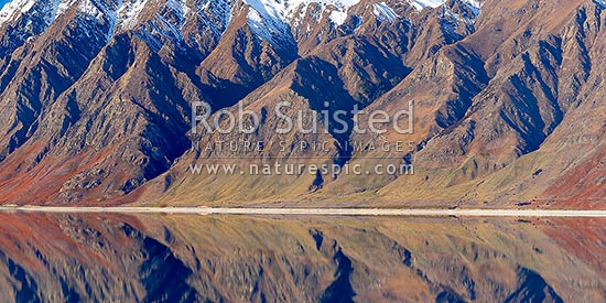 Lake Hawea with snow covered rugged mountains reflecting in lake. Panorama, Lake Hawea, Otago, Queenstown Lakes District, Otago Region, New Zealand (NZ) stock photo.
