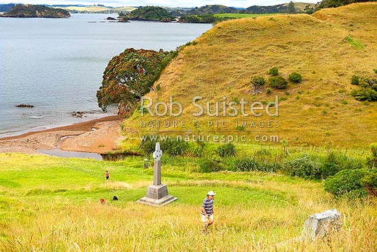 Marsden Cross and walkers in Hohi (Oihi) Bay, where Rev. Samuel Marsden preached his 1st sermon Christmas Day 1814, below Rangihoua Pa (top right), Kerikeri, Far North District, Northland Region, New Zealand (NZ) stock photo.