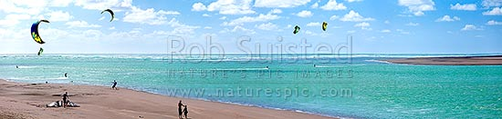 Kite surfers surfing at Wainamu Beach and the Raglan Bar and Raglan Harbour entrance. Panorama, Raglan, Waikato District, Waikato Region, New Zealand (NZ) stock photo.