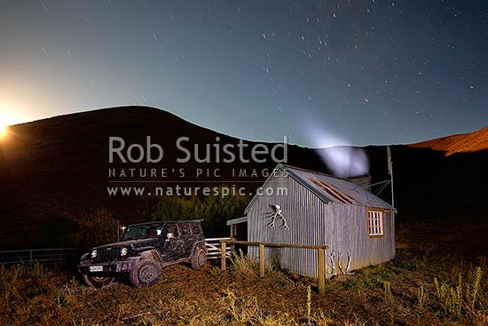 Half Moon Hut at night with star trails above. Historic old musterers hut near the Dillion River, in Half Moon Stream. Moonrise, Molesworth Station, Marlborough District, Marlborough Region, New Zealand (NZ) stock photo.