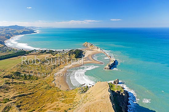 Castlepoint lighthouse, reef, lagoon and village, from above Castle Rock (162m). Aerial photo looking north to Cape Turnagain, Castlepoint, Masterton District, Wellington Region, New Zealand (NZ) stock photo.