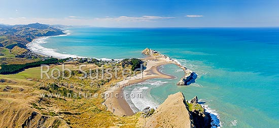 Castlepoint lighthouse, reef, lagoon and village, from above Castle Rock (162m). Castlepoint Scenic Reserve. Aerial panorama, Castlepoint, Masterton District, Wellington Region, New Zealand (NZ) stock photo.
