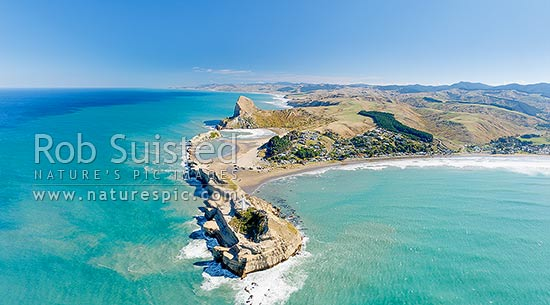 Castlepoint lighthouse, reef, lagoon and village, and Castle Rock (162m). Castlepoint Scenic Reserve. Aerial panorama looking south, Castlepoint, Masterton District, Wellington Region, New Zealand (NZ) stock photo.