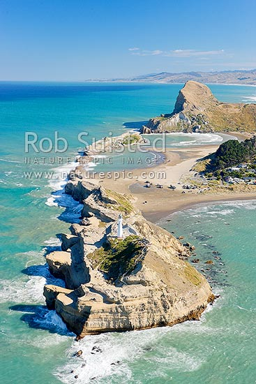 Castlepoint lighthouse, reef, lagoon, village, and Castle Rock (162m). Castlepoint Scenic Reserve. Aerial photo looking south, Castlepoint, Masterton District, Wellington Region, New Zealand (NZ) stock photo.