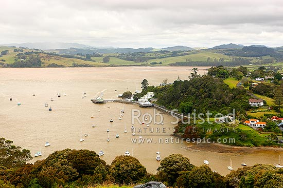 Mangonui township and harbour, seen from Rangikapiti Pa. Heavy rain and flooding with discoloured harbour, Mangonui, Far North District, Northland Region, New Zealand (NZ) stock photo.