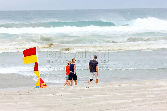 Beach walkers on Pakiri Beach, near surf lifesaving patrol flags, Pakiri Beach, Rodney District, Auckland Region, New Zealand (NZ) stock photo.