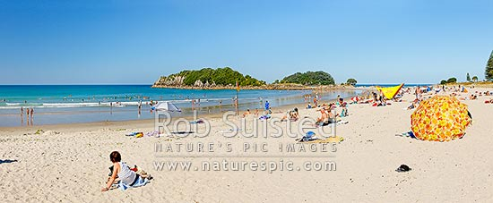 Mount Maunganui beach panorama, with people sunbathing and swimming, with Moturiki and Motuotau Islands behind, Mount Maunganui, Tauranga District, Bay of Plenty Region, New Zealand (NZ) stock photo.