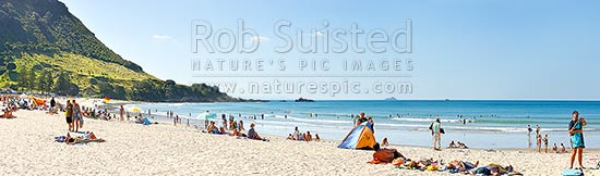 Mount Maunganui beach panorama, with people sunbathing and swimming, and distant Karewa Island (centre) beyond. The Mount peak at left, Mount Maunganui, Tauranga District, Bay of Plenty Region, New Zealand (NZ) stock photo.