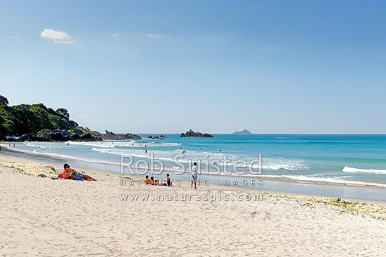 Mount Maunganui beach with people sunbathing and swimming, and distant Karewa Island (centre), Bay of Plenty, Mount Maunganui, Tauranga District, Bay of Plenty Region, New Zealand (NZ) stock photo.
