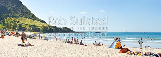 Mount Maunganui beach panorama, with people sunbathing and swimming, and distant Karewa Island (right) beyond. The Mount peak at left, Mount Maunganui, Tauranga District, Bay of Plenty Region, New Zealand (NZ) stock photo.