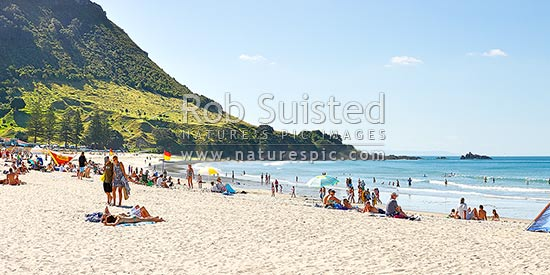Mount Maunganui beach panorama, with people sunbathing and swimming. The Mount peak at left, Mount Maunganui, Tauranga District, Bay of Plenty Region, New Zealand (NZ) stock photo.