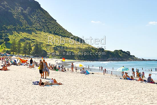 Mount Maunganui beach with people sunbathing and swimming. The Mount peak and walkway track at left, Mount Maunganui, Tauranga District, Bay of Plenty Region, New Zealand (NZ) stock photo.
