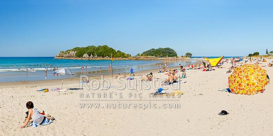 Mount Maunganui beach with people sunbathing and swimming, with Moturiki and Motuotau Islands behind, Mount Maunganui, Tauranga District, Bay of Plenty Region, New Zealand (NZ) stock photo.