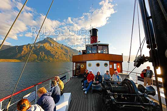 TSS Earnslaw, an historic steamship carrying tourists on Lake Wakatipu. Walter Peak (1800m) behind. Evening light, Queenstown, Queenstown Lakes District, Otago Region, New Zealand (NZ) stock photo.