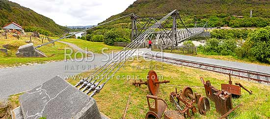 Brunner Suspension Bridge over the Grey River at the historic Brunner Mine Site, one of NZ's earliest industrial sites from 1860's onwards. Stillwater. Panorama, Taylorville, Grey District, West Coast Region, New Zealand (NZ) stock photo.