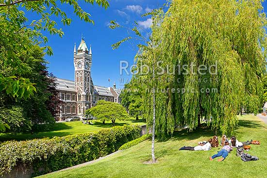 University of Otago Registry Building (Clock tower), built in 1879, seen from across the Water of Leith (River), with people enjoying sumertime amongst gardens, Dunedin, Dunedin City District, Otago Region, New Zealand (NZ) stock photo.