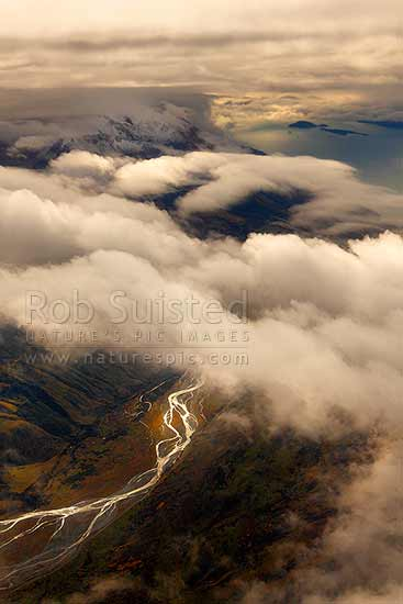 The Von River glistening under cloud on Mt Nicholas Station. Lake Wakatipu with Pigeon and Pig Island above. Moody aerial, Queenstown, Queenstown Lakes District, Otago Region, New Zealand (NZ) stock photo.