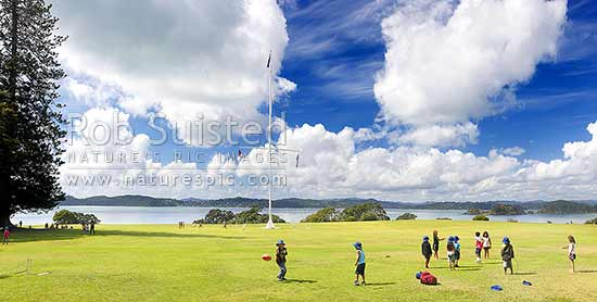 Waitangi Treaty Grounds with visiting school children playing on grass. Naval flagstaff standing where Te Tiriti o Waitangi (Treaty of Waitangi) was signed. Panorama, Waitangi, Bay of Islands, Far North District, Northland Region, New Zealand (NZ) stock photo.