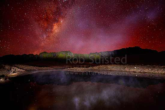 Milky Way galaxy above a steaming alpine tarn on a frosty winter evening. Beech tree forest (Fuscospora sp.) lit by torch light. Cannan Downs, Abel Tasman National Park, Tasman District, Tasman Region, New Zealand (NZ) stock photo.